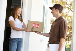 Frau an Haustür mit Paketbote Bild: A handsome young delivery man delivering a package: Stephen Coburn, Shutterstock http://www.shutterstock.com/pic-26078896/stock-photo-a-handsome-young-delivery-man-delivering-a-package.html